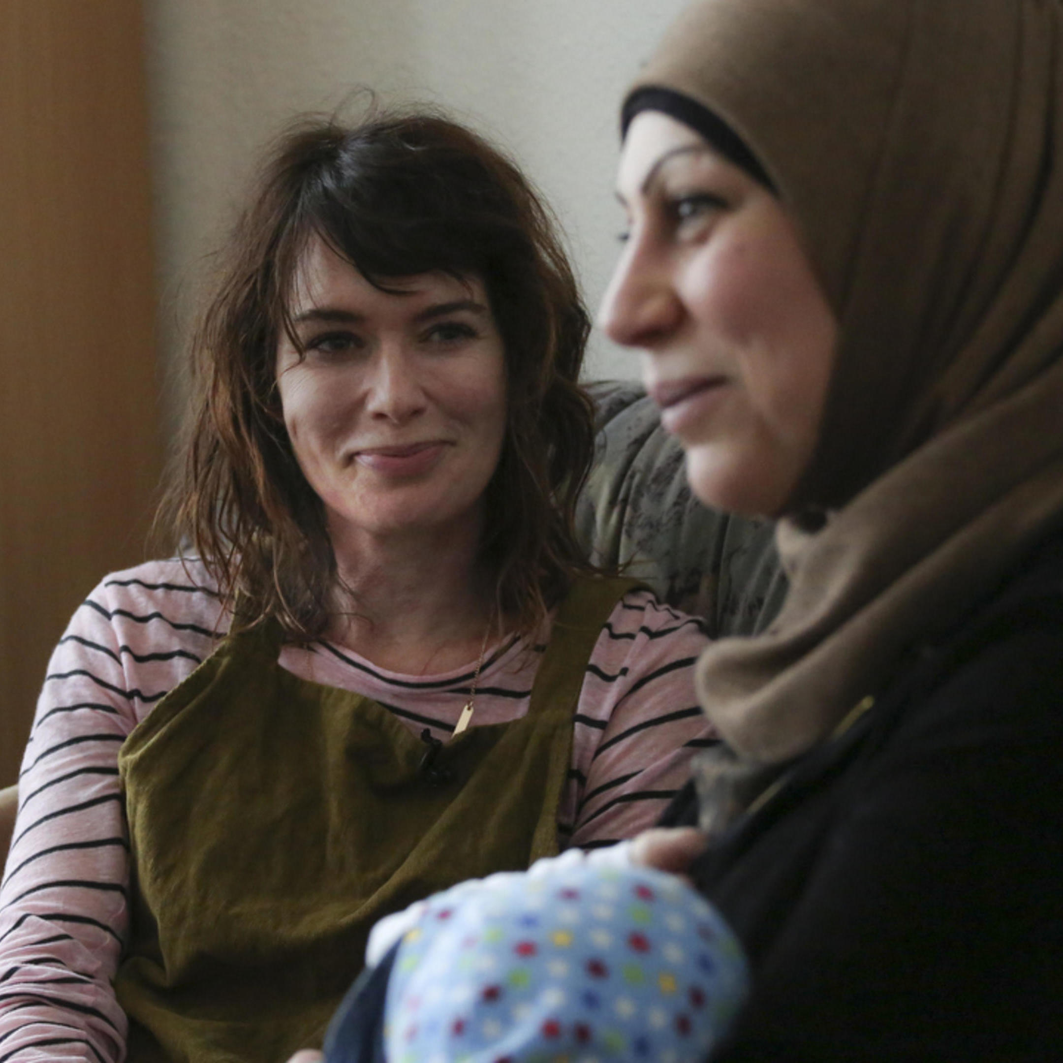 Lena Headey sits with refugees in Germany